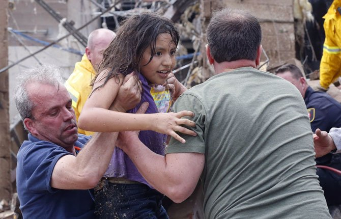 A child is pulled from the rubble of the Plaza Towers Elementary School in Moore, Okla., and passed along to rescuers May 20. A tornado as much as a mile wide with winds up to 200 mph roared through the Oklahoma City suburbs Monday, flattening entire neighborhoods, setting buildings on fire and landing a direct blow on an elementary school.