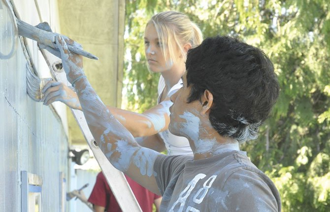 Angel Esquio and Alissa Pastor spread a fresh coat of paint onto Imogene Abram's house as part of a service project put on by student leaders at The Dalles Wahtonka High School. 	Jade McDowell photo