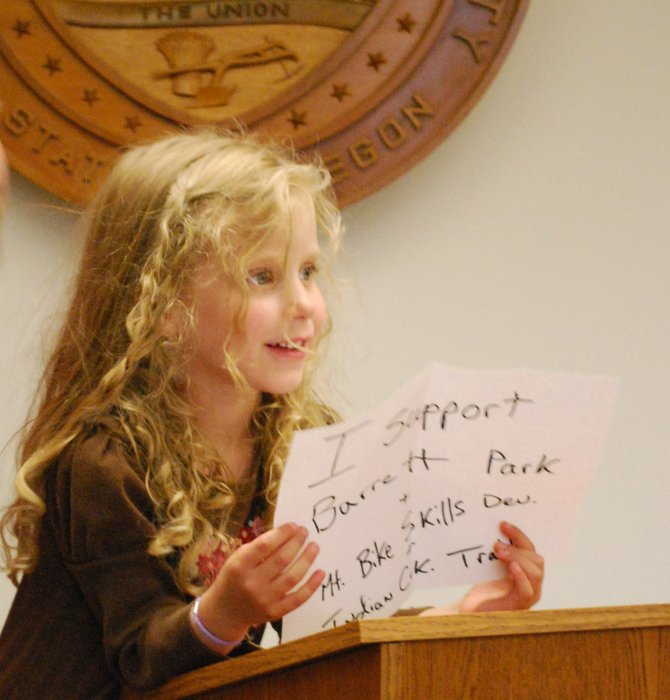 A cadre of Barrett Park supporters turned out in hope of encouraging Hood River County Commissioners to reconsider approval of the proposed park. Sophia Stromquist of Hood River, shown here, jumped atop a meeting room chair, spoke up and displayed her homemade sign during the public comment period. Commissioners considered park litigation details during their closed session.