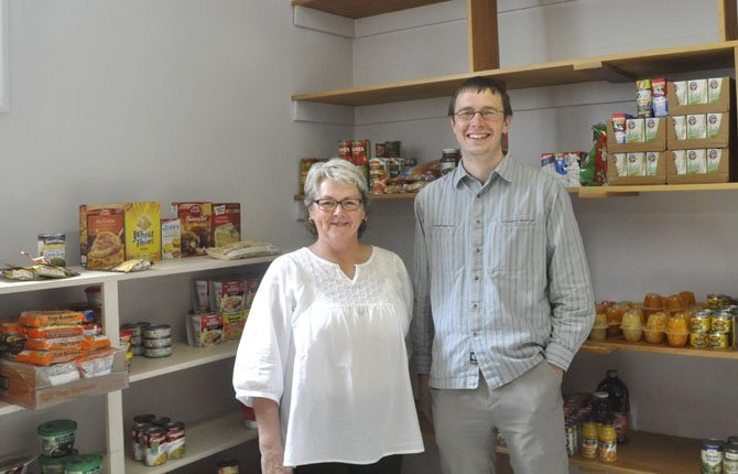 Glenis SchReffler and Tyler Beane, interim pastor for First United Methodist Church, show the food storage area where supplies are kept for the new backpack program that is feeding homeless students at The Dalles Wahtonka High School.
