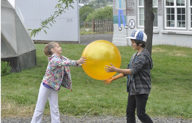 "Alexandria McAllister, left, and Silas Fields pass a big yellow ""sun"" around the circle in a game of hot potato during the school's No Fry Day."
