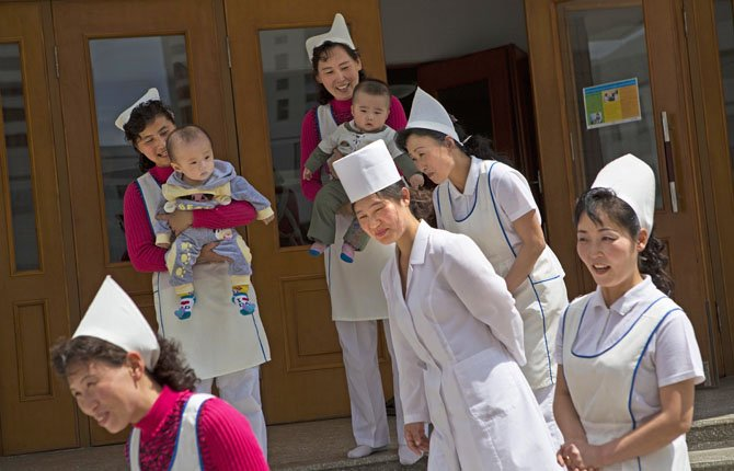 North Korean nurses say goodbye to representatives from foreign humanitarian agencies after a U.N. and North Korean government program to give vitamin supplements and deworming pills to children at a nursery school in Pyongyang, North Korea on Child Health Day.
