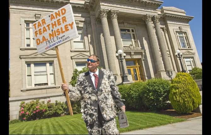 Dressed in a feather-coated suit, Gary West protests outside the Wasco County Courthouse Thursday morning, May 30.