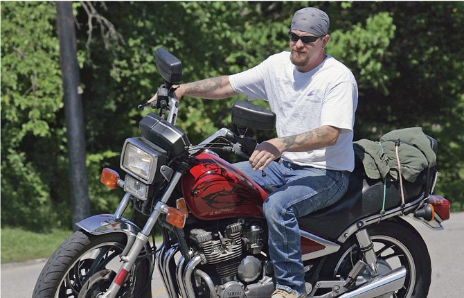 In this June 12, 2008 file photo, Randy Knauff takes off from work without a helmet on his motorcycle in Harmony, Pa. Across the nation, motorcyclists opposed to mandatory helmet use have been chipping away at state helmet laws for years while crash deaths have been on the rise.