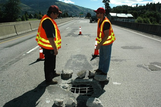 ODOT maintenance specialists Doug Gross (left) and Cameron Kersavage prepare to remove concrete debris from a hole in the I-84 Hood River overpass near milepost 64. Kersavage points out the river visible below the damage.