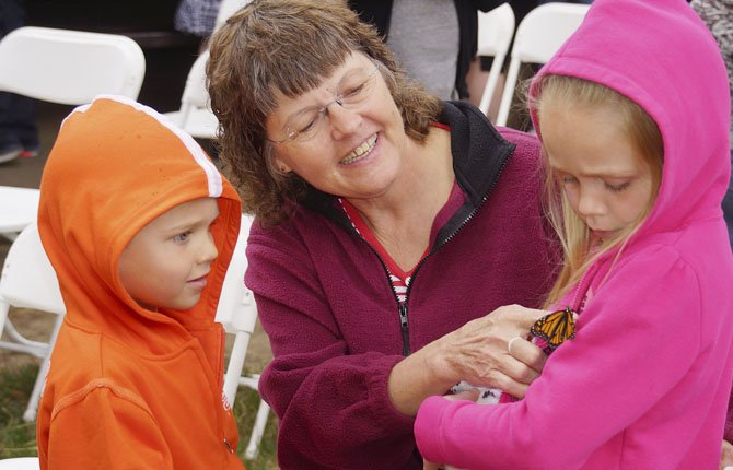 A young girl gets a helping finger from an adult during the fifth annual Heart of Hospice Butterfly Release, which honors the loss of loved ones.