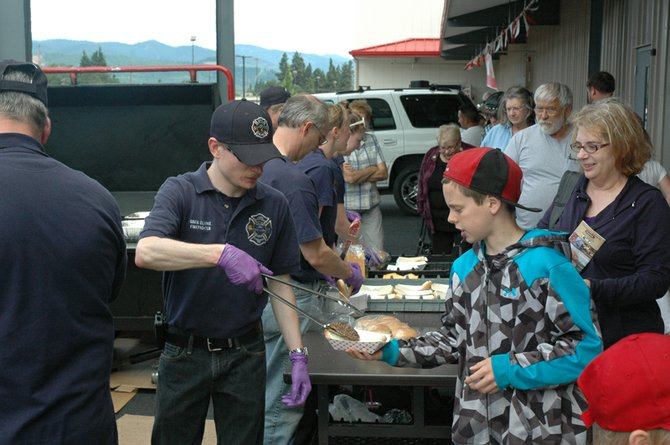 Dean Rockett, 12, accepts a hamburger from Greg Clarke at the West Side firefighters' barbecue at Hood River Supply's grand opening Saturday.