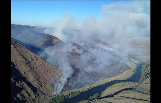 INVESTIGATORS BELIEVE a wildfire that has consumed 3,300 acres along the Lower Deschutes River was human caused and not started by lightning. The blaze is expected to be fully contained by Wednesday evening if winds do not pick up in the current hot and dry weather conditions.