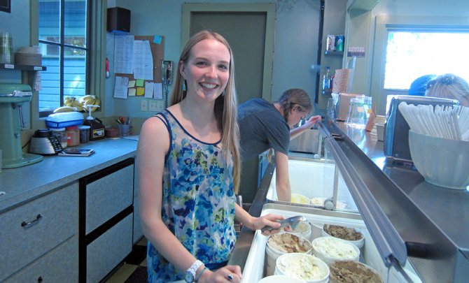 2013 grad Molly Clarke stands ready at Mike's, where delicious frozen treats await, and employees post the traditional tip wish list.