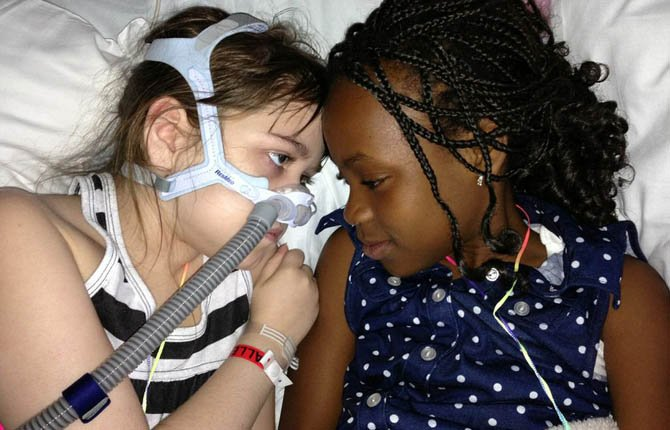 In this May 30, 2013 file photo provided by the Murnaghan family, Sarah Murnaghan, left, lies in her hospital bed next to adopted sister Ella on the 100th day of her stay in Children's Hospital of Philadelphia.