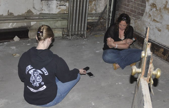 INVESTIGATOR Heather Maurin, right, reports a cold feeling and a sense that someone is sitting beside her as she and Miranda Pollock attempt to communicate with ghosts in the vacant upstairs of a downtown The Dalles building. At top right, Pollock uses a gauge to seek out electromagnetic field readings.