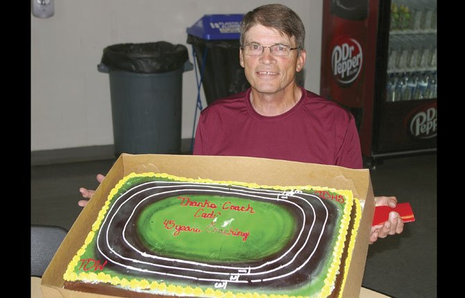 RECENTLY retired coach Bill Caddy displays the going-away cake given to him during Thursday's end-of-the-year track and field banquet. Caddy had an emotional moment when finally deciding to hang up his whistle after 45 years.