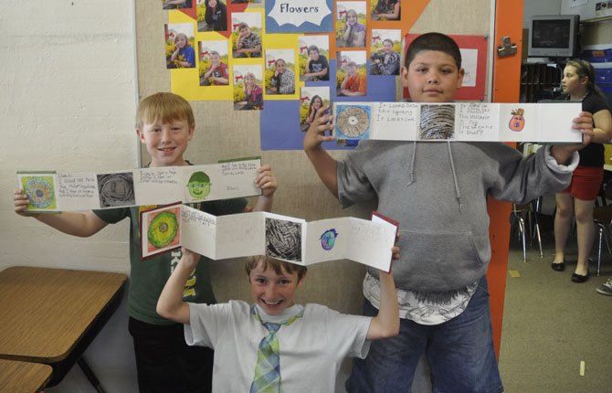 Isaac Lafrenz, Jeremy Williams and Jose Alvarez (left to right) show off their books they made about themselves as part of a grant to Colonel Wright teacher Teal Everts from the Wasco County Cultural Trust.