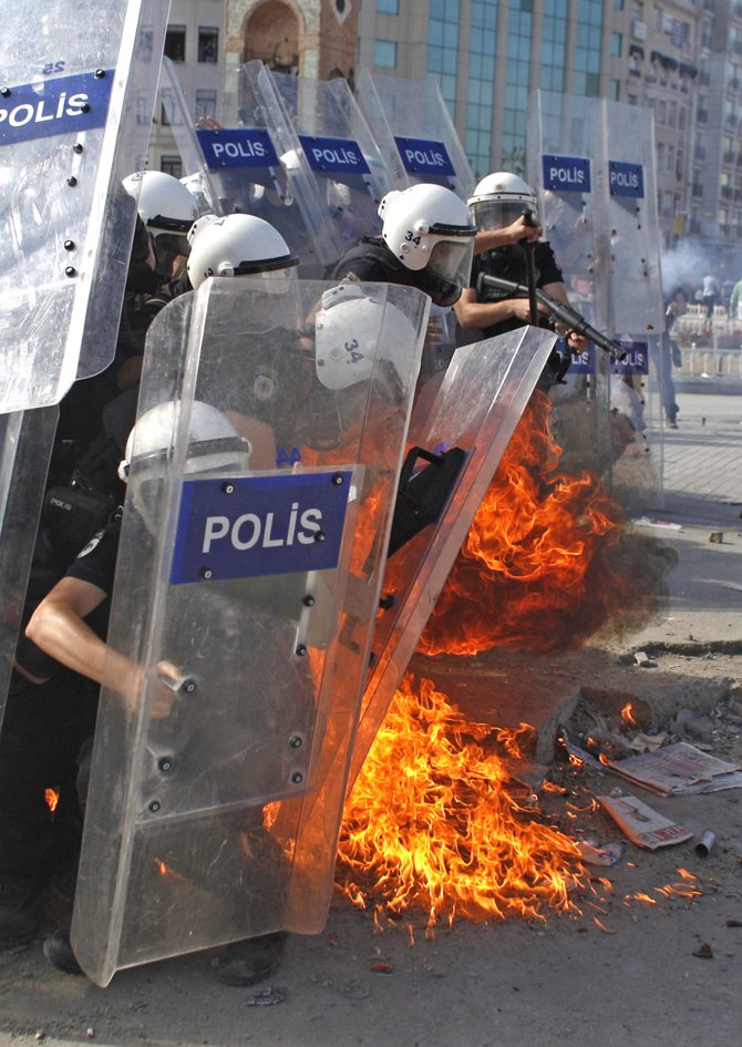 A petrol bomb explodes in front of  riot policemen during clashes in Taksim Square in Istanbul, Turkey, Tuesday, June 11, 2013. Hundreds of police in riot gear forced through barricades in Istanbul's central Taksim Square early Tuesday, pushing many of the protesters who had occupied the square for more than a week into a nearby park.