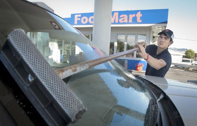 Kevin Lane swipes a windshield clean at the Downtown 76 station, Third and Lincoln in The Dalles. The city is considering asking voters to approve raising the city gas tax from three cents to six cents per gallon.