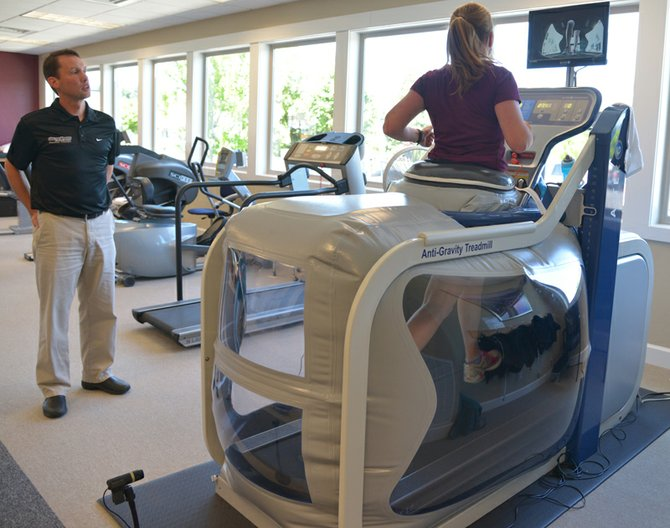 Kateri Lohr uses Gorge Spine and Sports Medicine's new anti-gravity treadmill to get in a running workout while rehabbing an injury. Physical Therapist Tom Moline watches Lohr's form using a live-view camera pointed inside the pressurized bubble.