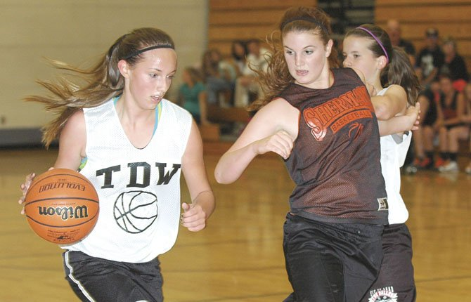 THE DALLES WAHTONKA forward Brooke McCall (left) uses a screen set by a teammate to slip past Sherman's Katie Poirer during Thursday's summer hoops exhibition at The Dalles Middle School. In this part of the season, coaches can observe young talent and institute new plays for the winter campaign.