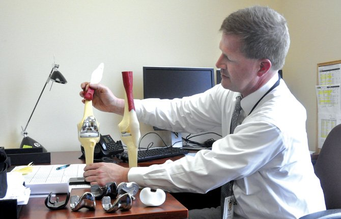 Dr. Mark Cullen, an orthopedic specialist at Water's Edge, shows various knee replacement devices at his office.