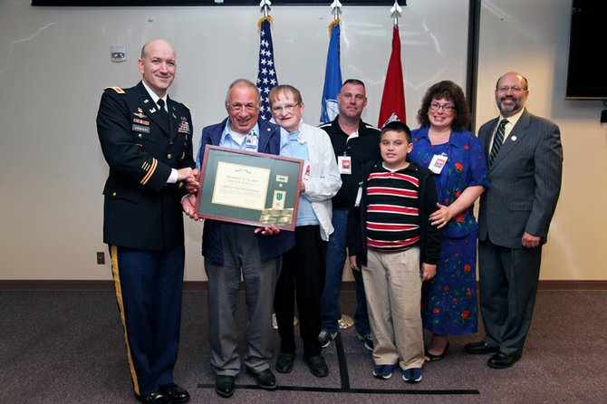 Joe Renault accepts his honor from Col. John Eisenhauer, commander, Portland District, U.S. Army Corps of Engineers, left, and Kevin Brice, deputy district engineer for programs and project management, far right. With Joe are his wife, Nancy, and children Michial and Angelia, and Angelia's son, Devin.