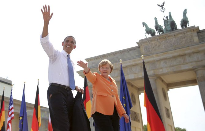 US President Barack Obama waves to spectators before he delivers a speech in front of the Brandenburg Gate at Pariser Platz in Berlin, Germany, June 19. At right stands German chancellor Angela Merkel.
