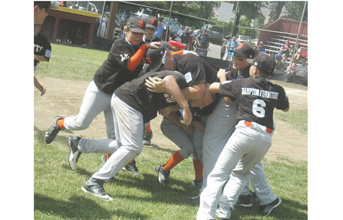 HAMPTON FURNITURE Giants come together for a dog pile on coach Mike Eiesland after clinching The Dalles Little League Majors championship Saturday at Kramer Field in Thje Dalles. In the game, the Giants led by as much as 5-1, and held off a late Athletic ralley to post a 6-4 triumph.