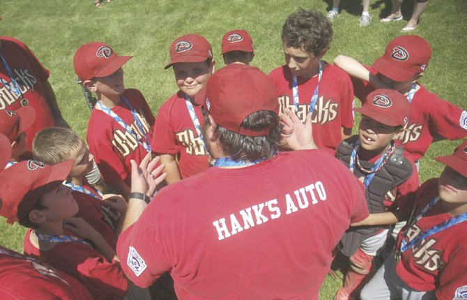 Hank's Auto D-Backs coach Nick DeLeon (middle) congratulates his team in a huddle after his squad pulled off a 12-1 mercy-rule win over the Pirates Saturday, June 15 in Minors baseball action.