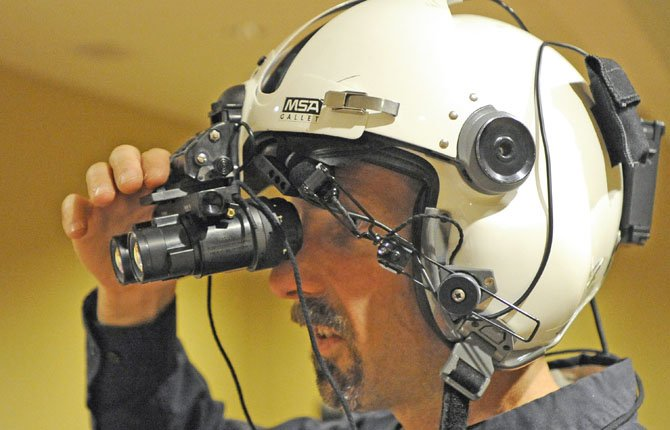 Jared Douglas, assistant chief flight instructor at Leading Edge Aviation, makes adjustments to his night-vision goggles prior to a flight Tuesday night June 11 at Bend Municipal Airport.
