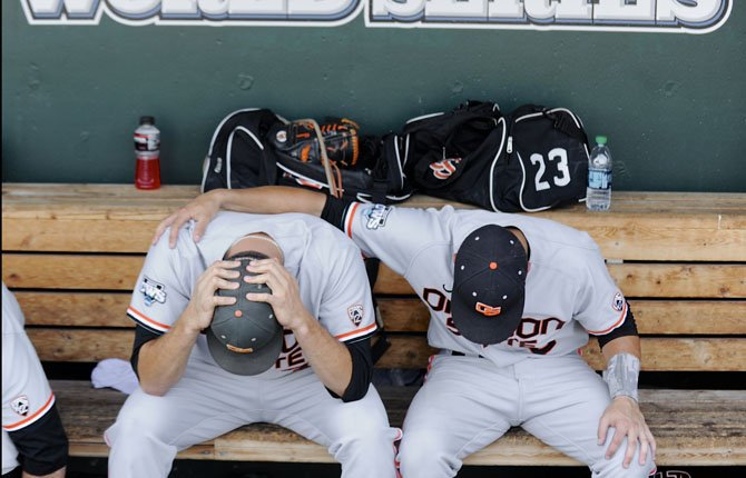 Oregon State's Matt Boyd, left, and Nate Esposito sit in the dugout after losing 4-1 to Mississippi State in an NCAA College World Series baseball game in Omaha, Neb., Friday, June 21, 2013. Mississippi State advances to the championship series and Oregon State is eliminated.