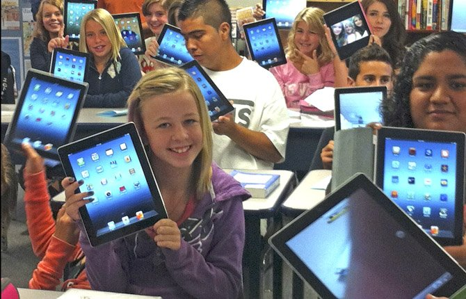 Students at Mosier Middle School, a charter school, hold up iPads they use to learn.