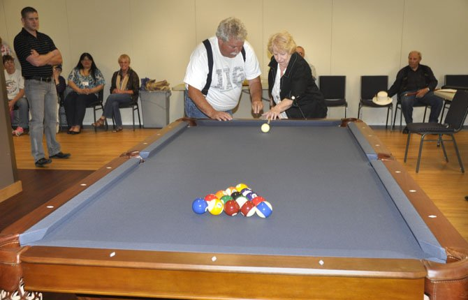 DARLENE DORIS gets a tip from Ralph Fawcett about how to make the opening break for a game on the new billiards table at the Oregon Veterans' Home. The table was purchased with donations after Darlene's late husband, Jimmie, came up with the fundraising plan.