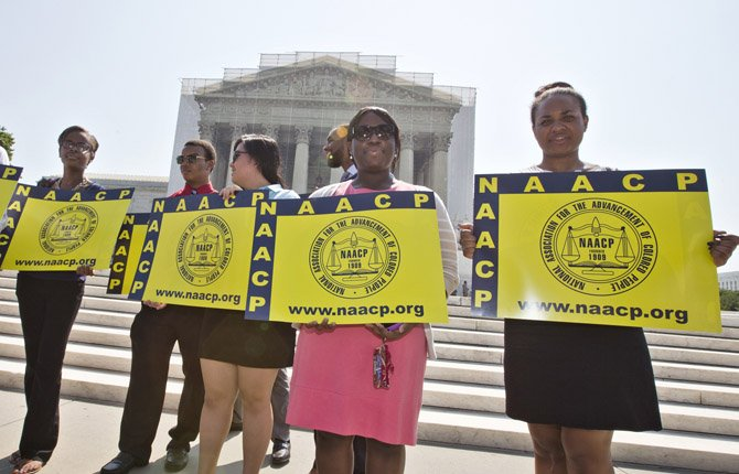 Representatives from the NAACP Legal Defense Fund stand outside the Supreme Court in Washington, June 25.