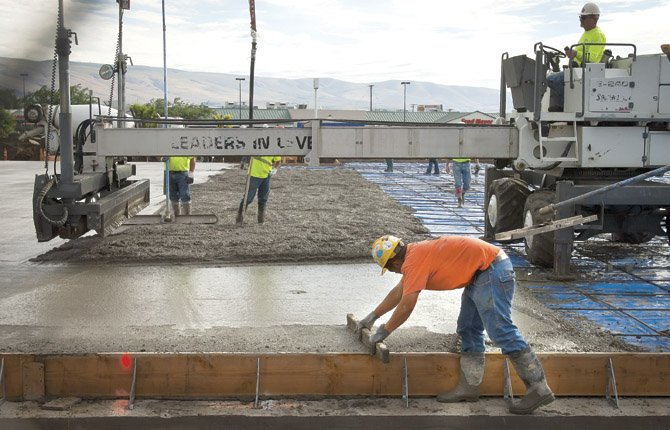Crews smooth freshly-poured concrete, and touch up the edges, as construction of the new Goodwill Industries store in The Dalles continues Thursday morning, June 27. The building, which is expected to open in October or November, will be located on the south side of the lot.