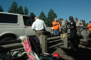 Bronco owner Louis Hooks, center, talks with investigators as they look through belongings the suspect tried to load from a stolen pickup into Hooks' vehicle, along I-84.