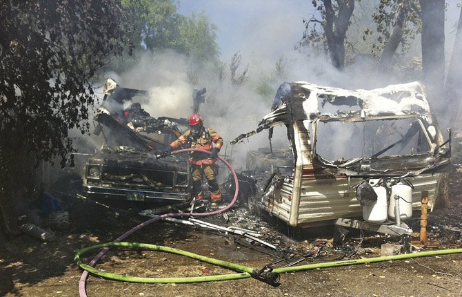 A firefighter wets down a pickup truck with a burned out bed and a travel trailer early Friday afternoon. Houses to either side of the parked vehicles were undamaged, and the fire was rapidly extinguished by local fire crews.