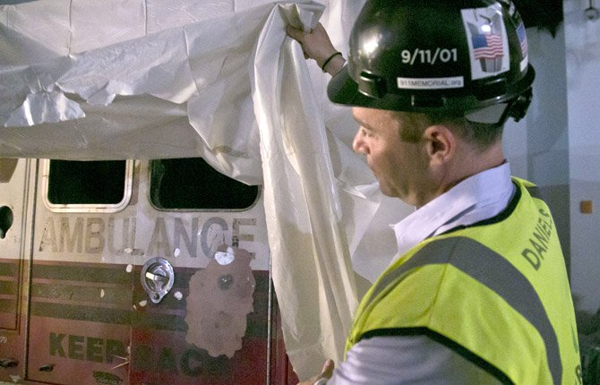 JOE DANIELS, 911 Memorial President, lifts the cover for a glance of an ambulance during a tour of the 911 Memorial Museum on June 27 in New York. Recovered from the World Trade Center after September 11, 2001, the vehicle will be part of the museum's permanent installment.