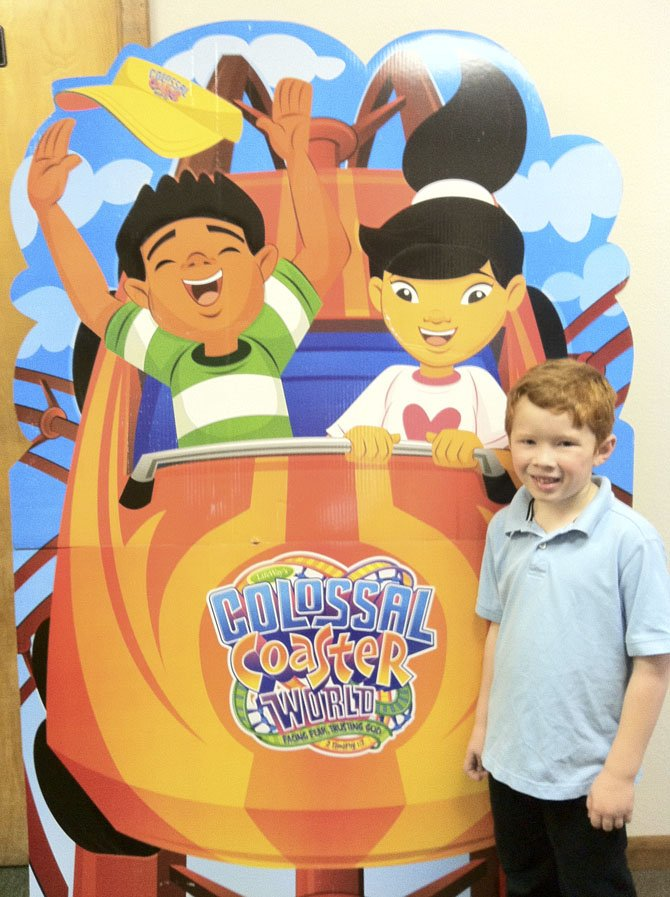 Jackson Warren, 6, stands in front of a large poster advertising the upcoming Vacation Bible School at Emmanuel Baptist Church, to be held July 8-12.