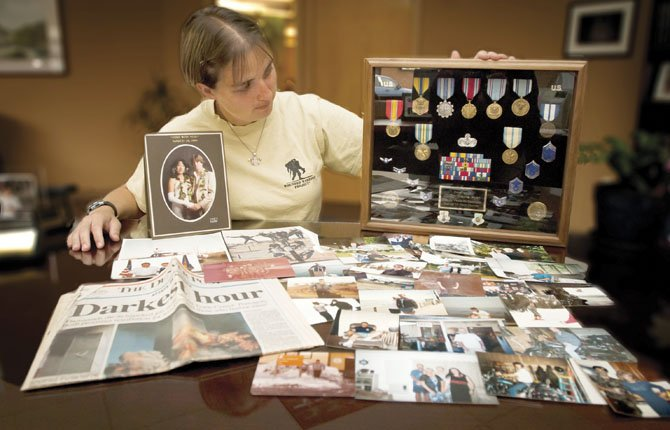CHEYENNE HERON, shown with photos, clippings and medals from the life of the late Wayne Ryan, is campaigning to have his death from alcoholism linked to post-traumatic stress disorder.