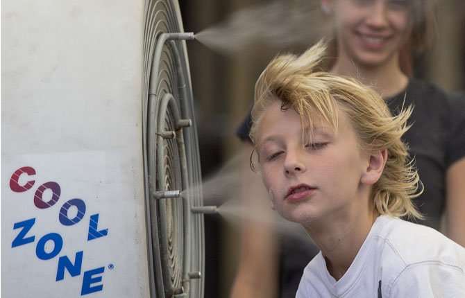 Ten-year-old Easton Martin, of Mesa, Ariz., stops to cool off in a misting fan while walking along The Strip with his family June 28 in Las Vegas.  A blazing heat wave sent the mercury soaring over the West starting Friday, threatening to ground airliners and raising fears that people and pets will get burned on the scalding pavement.
