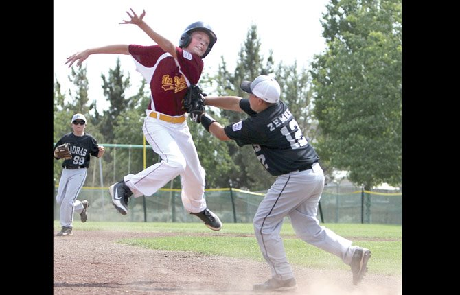 THE DALLES all-star Zach Anderson, of the 11U squad, tries to avoid a tag from the Jefferson County third baseman in Little League All-Star action in Bend. TD plays Bend North in semifinal action at 8:15 a.m. Thursday.