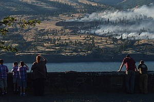 A couple peers from Memaloose Overlook at a wildfire burning across the Columbia River in Washington near Major Creek, which lies between Catherine Creek and Lyle. As of press time, the fire had burned 150 acres and was 40-percent contained, with full containment or near-full containment expected for Friday evening.