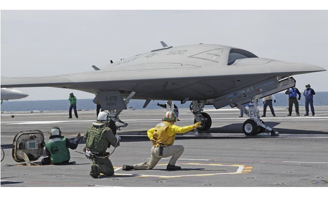 FILE - A Navy X-47B drone is launched off the nuclear powered aircraft carrier USS George H. W. Bush off the coast of Virginia, in this May 14, 2013 file photo. The Navy says the X-47B experimental aircraft will try to land aboard the USS George H.W. Bush on Wednesday July 10, 2013.