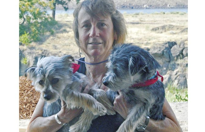 Yvonne Pepin-Wakefield poses with her two dogs outside of the home and art studio she and her husband are building in The Dalles. The artist said she can't wait to begin painting the view from her studio.