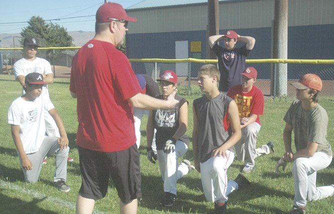 THE DALLES  Babe Ruth All Star coach Sean Herriges (front) goes over a practice schedule Monday at Quinton Street Ballpark in The Dalles. TD hosts a state tournament this weekend with games scheduled to go off at Kramer and Wahtonka Fields. The championship game will be played at 2 p.m. Saturday on Kramer Field with the winner advancing to regionals in Centralia, Wash.