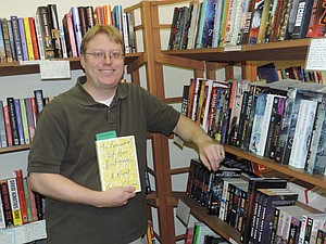 Muir Cohen holds a recent favorite in the science fiction section.