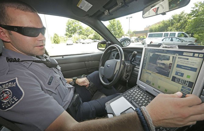 Office Dennis Vafier of the Alexandria Police Dept., uses a laptop in his squad car to scan vehicle license plates during his patrols, July 16, in Alexandria, Va. Local police departments across the country have amassed millions of digital records on the location and movements of vehicles with a license plate using automated scanners. Departments keep the records for weeks or even years.
