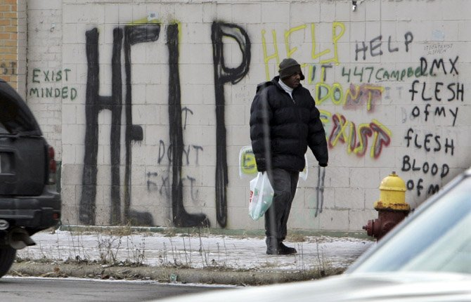 a pedestrian walks by graffiti in downtown Detroit in this Dec. 2008 file photo. On July 18 Detroit became the largest city in U.S. history to file for bankruptcy when State-appointed emergency manager Kevyn Orr asked a federal judge for municipal bankruptcy protection.