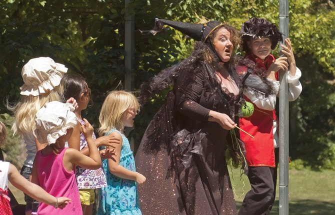 "THE EVIL Thirteenth Fairy (Linda Beiter), center, threatens to turn The Prince (Ben Garret), right, into a mouse as a grove of evil trees, left, looks on during the performance of ""Briar Rose"" at City Park in The Dalles July 20. The free performance was sponsored by State Farm Dean Dollarhide and The Theatre Company of The Dalles. The play was one of many activities that took place in the community during the annual Fort Dalles Days celebration."