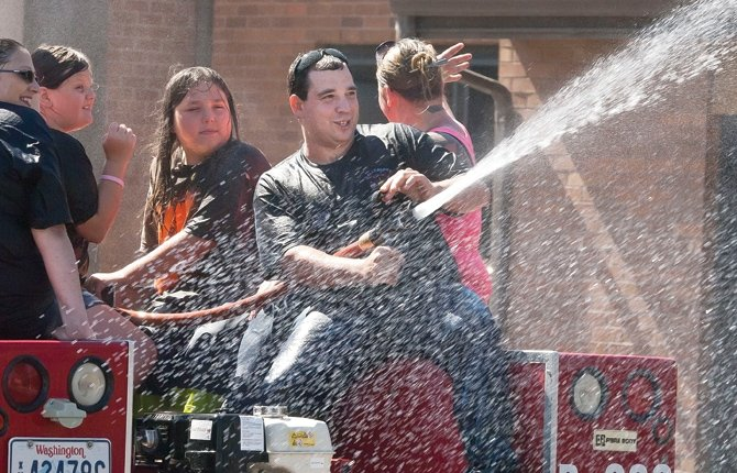 A VOLUNTEER onboard a Dallesport Fire fire truck replies to a soaking from a following fire truck with a blast from his own hose during the Rough and Wild Rodeo parade downtown The Dalles Saturday morning, July 20. 	Mark B. Gibson photo