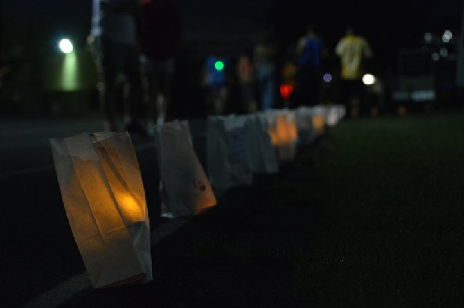 Luminary bags line the track at Hood River Valley High School. The bags are adorned with messages to loved ones who have been affected by cancer.