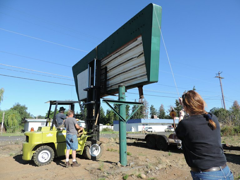 Donna Davidson of WAAAM helps guide the Trail Drive-In sign from its moorings on Tucker Road. Volunteers will renovate the sign, but it will take a year or so, according to Davidson.